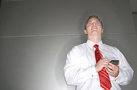 Low angle view of a businessman operating a personal data assistant