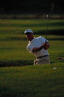 A mid adult man playing golf
