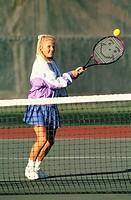 A teenage girl playing lawn tennis