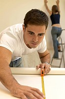 Close_up of a young man measuring a roll of wallpaper with a woman on a step ladder behind him