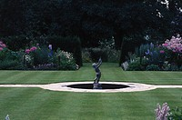View of a statue in the center of a manicured garden