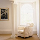A white sofa in a corner near a carved pillar