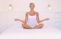Young woman doing yoga on a bed
