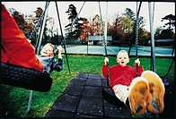Kids swinging at the playground (thumbnail)