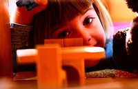 little girl playing with toy furniture