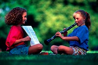 girl practicing the clarinet with a friend