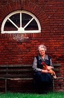 elderly woman holding a rooster