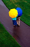 elderly couple walking in the rain