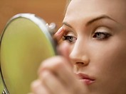 woman with hand mirror and eye liner