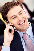 Business man on the phone smiling at his office