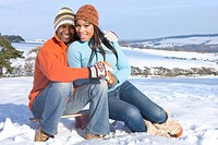 Couple sitting on sled in snowy field