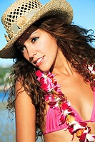 Hawaii, Oahu, Attractive young woman on the beach wearing a straw hat.