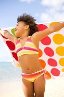 Hawaii, Oahu, Adorable little girl holding a polka_dot towel along the waters edge.