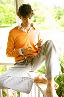 Hawaii, Portrait of a European Male Model in orange sweater eating papaya.