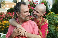 Married same sex gay couple embracing and looking affectionately at each other while sitting in the garden of their home