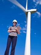 Mixed race businesswoman standing near wind turbine
