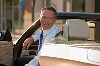 Caucasian businessman smiling in convertible