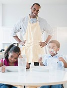African American father preparing dinner for children