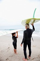 Hispanic grandfather and grandson carrying surfboards