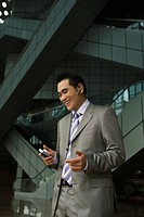 Chinese businessman talking on cell phone with hands_free device