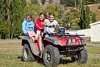 Upcot Station girls with pet spaniel ride quad bike on farm, Upper Awatere valley, Marlborough, New Zealand.