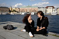 Two local girls relax in the harbor with the 19th century Grand Hotel in the background, Stockholm, Sweden