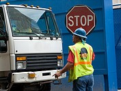 A construction company employee directs incoming working trucks to the construction site  He is wearing a safety vesy,helmut and holding a stop sign