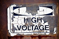 cracked weathered sign that says high voltage