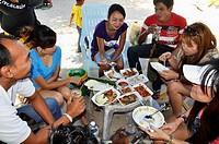 Pattaya (Thailand), Thai family eating along the sidewalk at Pattaya Beach