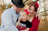 This photo is a small young family with mother, father and toddler girl, mom and daughter are wearing red bows while dad embraces both Background is i...