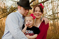 This cute young family is a father embracing his wife and young daughter and they are both wearing red bows in their hair Background is intentionally ...