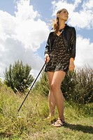 woman contemplating on a golf shot from deep rough