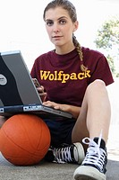 woman texting with laptop on top of a basketball