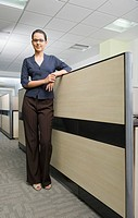 Portrait of a businesswoman leaning against a cubicle wall in an office