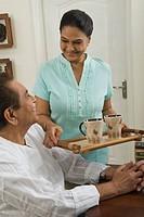 Woman bringing tea for a man