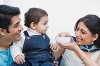 Couple feeding baby food to their son