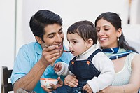 Couple feeding baby food to their son