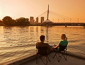 couple on dock along the Red River, Winnipeg skyline from St. Boniface, Manitoba, Canada