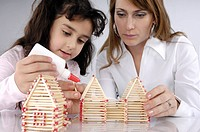 Mother and daughter building house from matches together
