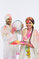 Man playing a tambourine with a woman holding a tray of Holi colors