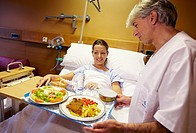Nurse with food tray and patient in a hospital room. Hospital Policlinica Gipuzkoa, San Sebastian, Donostia, Euskadi, Spain