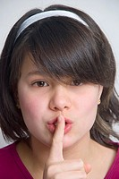 Young 11 year old girl with finger to lips