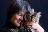 Mature woman with pet domestic male Siberian Forest cat