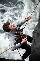 Learning the ropes: Aberystwyth university students abseiling on the sea wall, training for climbing , Wales UK