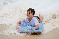 Young Brazilian boy playing on surf board on Copacabana Beach in Rio de Janeiro in Brazil