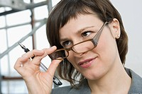 Close_up of a businesswoman holding eyeglasses and smirking