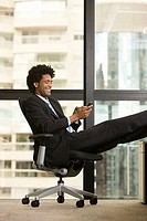 Businessman text messaging on a mobile phone in an office