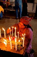 A woman prays by candlelight in an old cathredal in Chichicastenango, Guatemala.