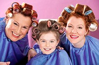 portrait of child and two women with curlers in their hair