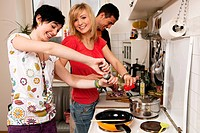 three friends in kitchen cooking together